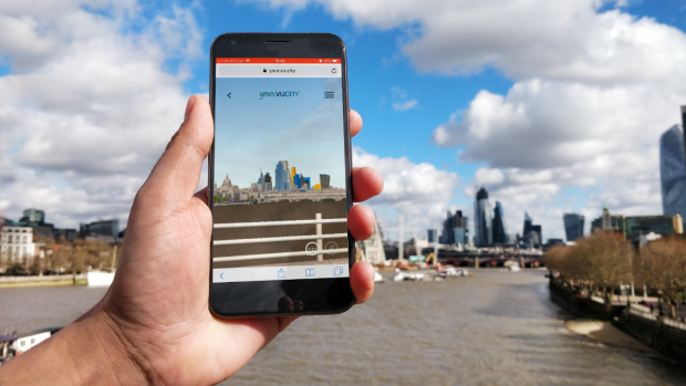 A hand holding a phone depicting the VU.CITY app with a backdrop of the river thames and London skyline.