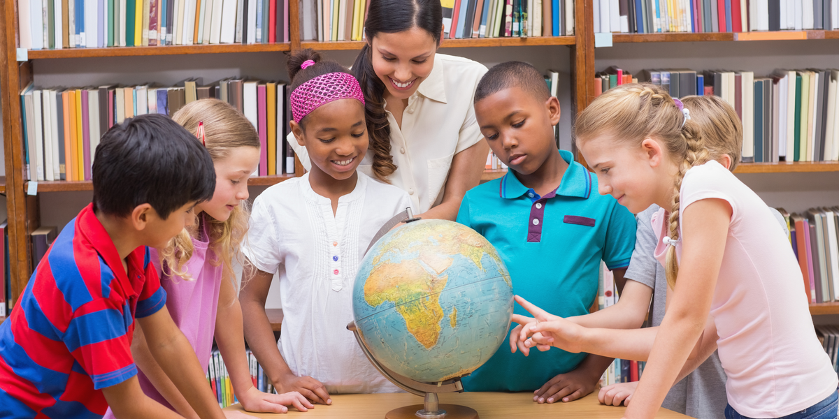 Multi ethnic children and teacher looking at globe in the library