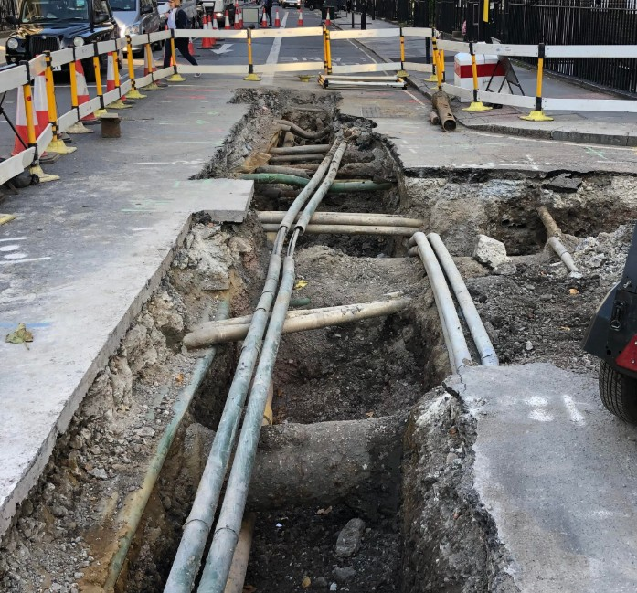 Road works in a London street showing pipes and cables