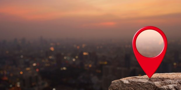 Red location icon on a rock overlooking a act at sunfall