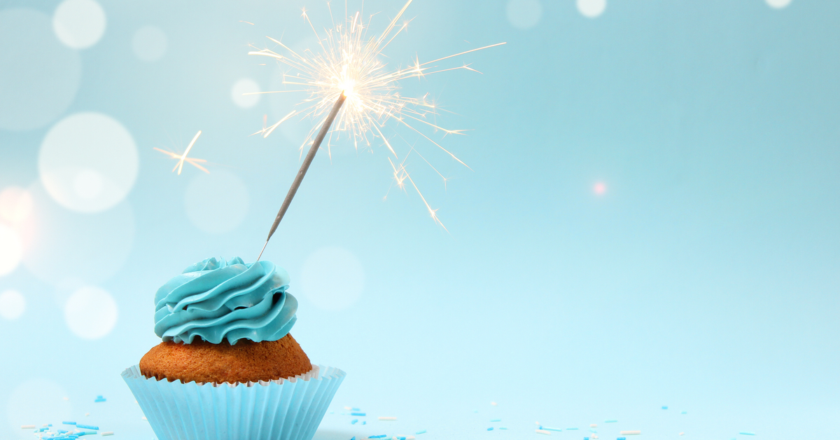 Cupcake wth one sparkler on a blue background